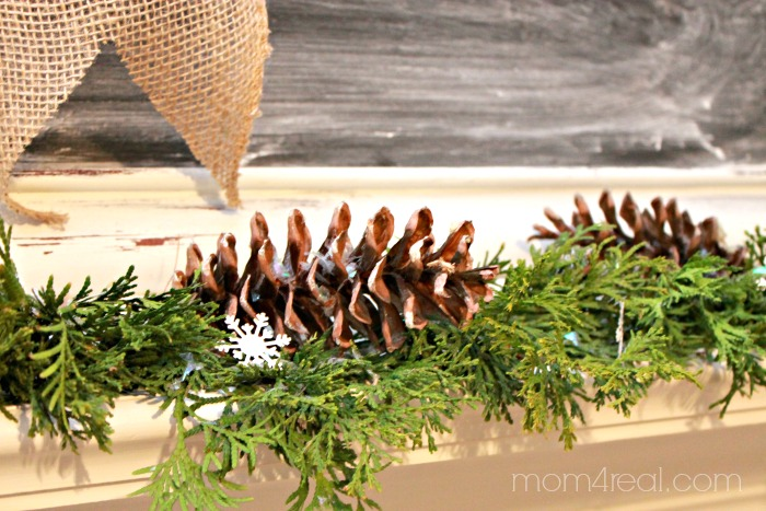 Pine cones and arborvitae across a mantel