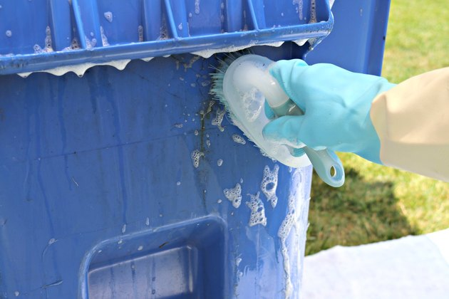 scrubbing an outdoor garbage can