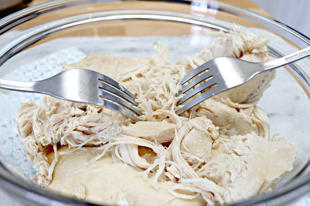 shredding chicken in a bowl using two forks