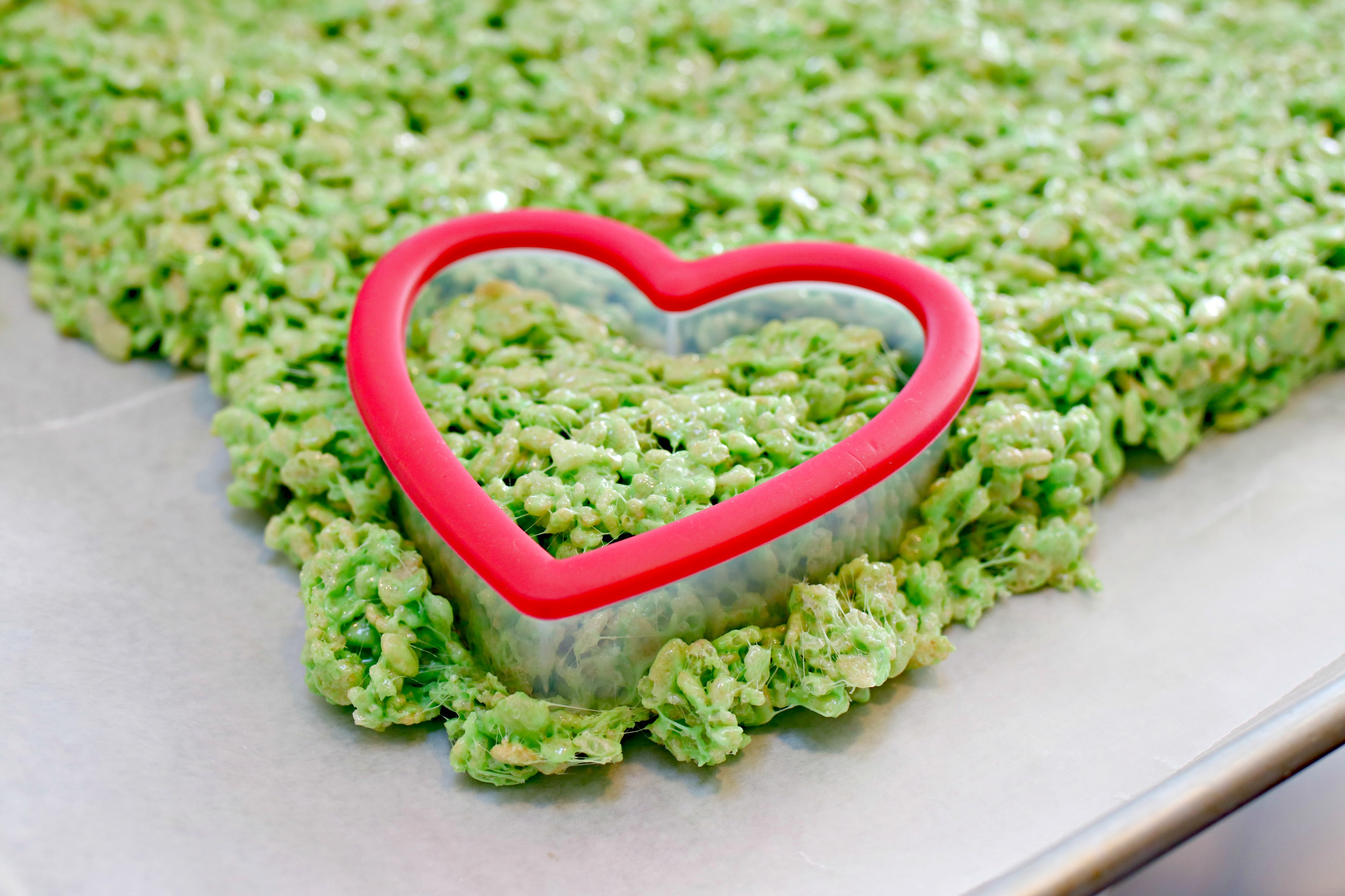 heart shaped cookie cutter cutting green Rice Krispie Treats