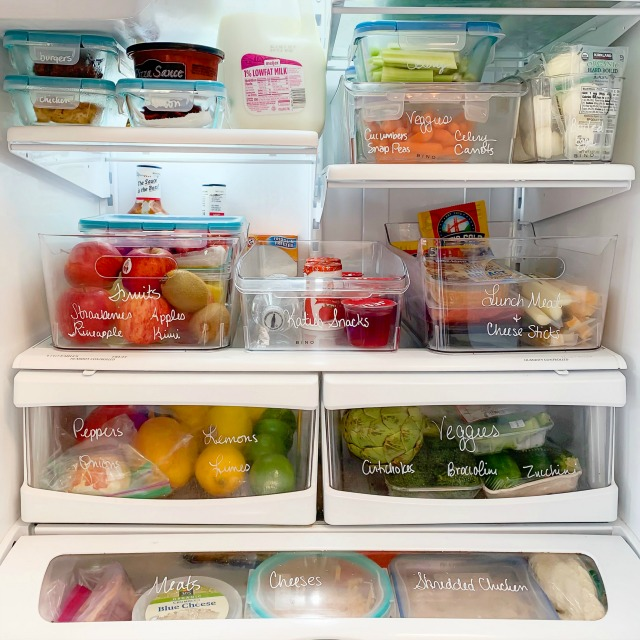 Organized refrigerator with clear plastic bins.