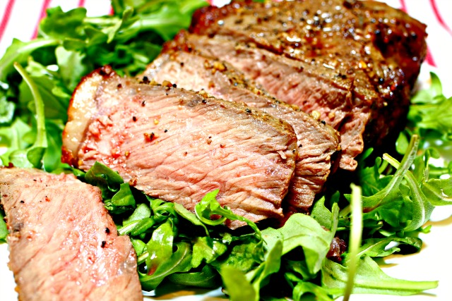 sliced New York strip steak on arugula
