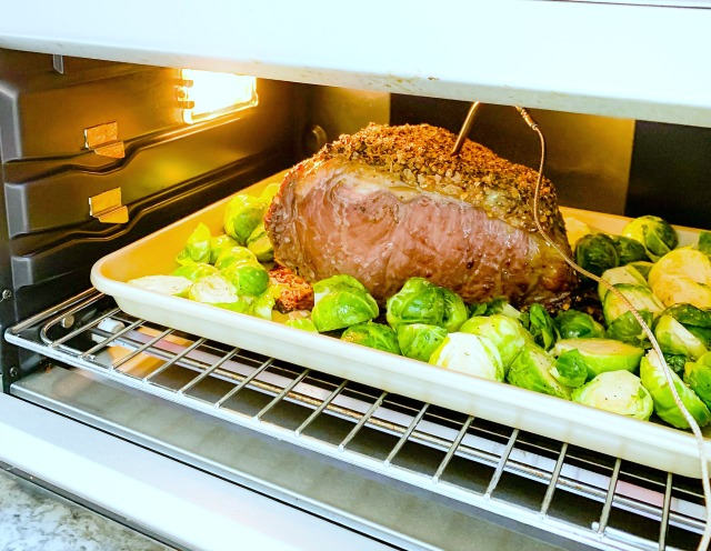 strip loin roast and brussels sprouts cooking in a toaster oven