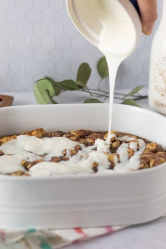 pouring icing over french toast casserole